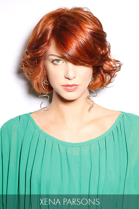 """Side-swept bangs that delicately graze the cheekbone are the """"mane"""" attraction of this flirty bob and flamboyant red hue."""