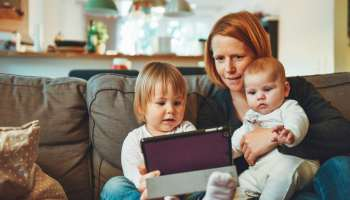 Mother showing a tablet with learning apps to her kids