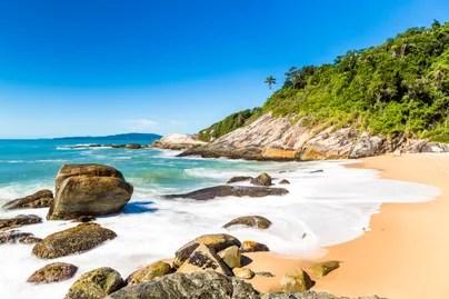 Pedras e vegetação na beira da praia, no canto da Praia do Estaleirinho.