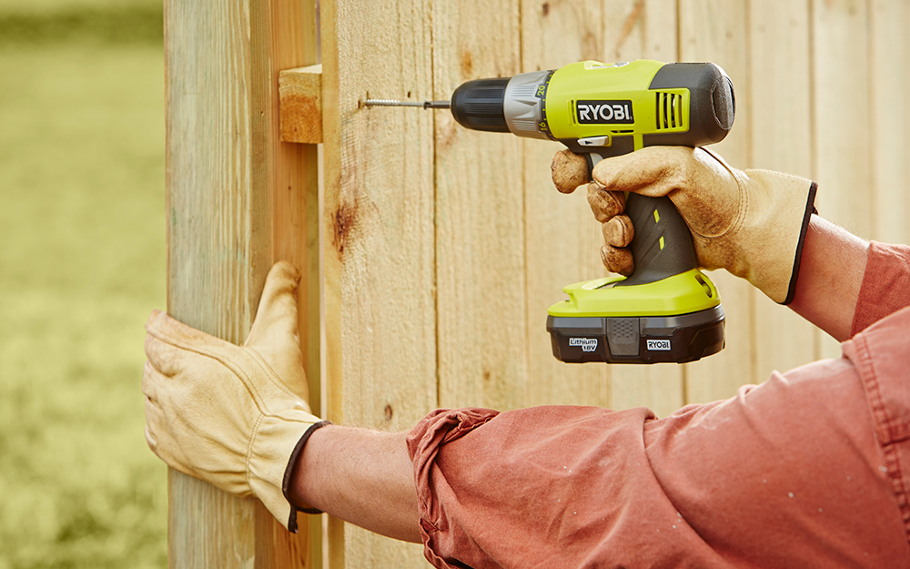 Person drilling nail into rails or panels of fence post with a Ryobi drill.