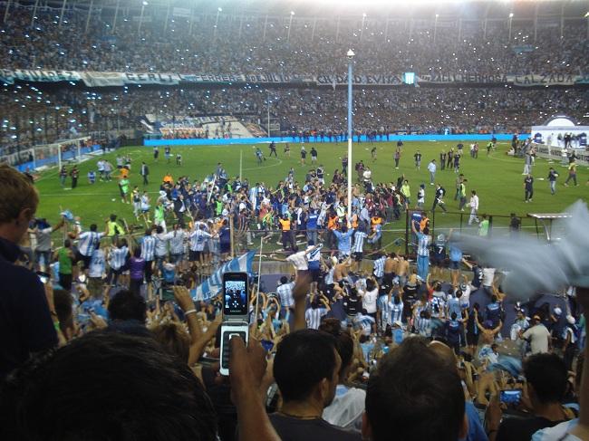 Volta olímpica: hinchas se penduram nas grades e sobem nas muretas para festejar Milito