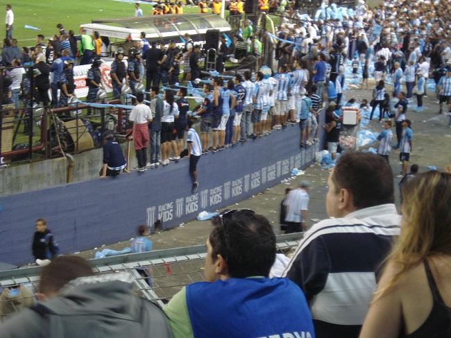 Torcedores sobre o muro que separa o campo da platéia acompanham a partida