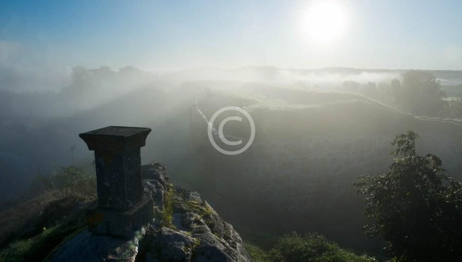 Steinstolpe ved klokketårnet i tåke