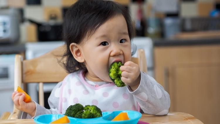 Asian child eating broccoli - Istock - Istock