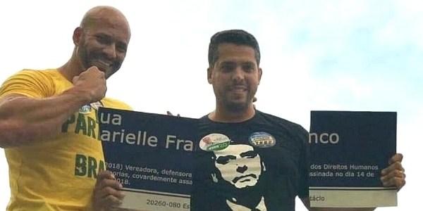 Rodrigo Amorim (à dir.) sorri ao exibir placa destruída em homenagem a Marielle