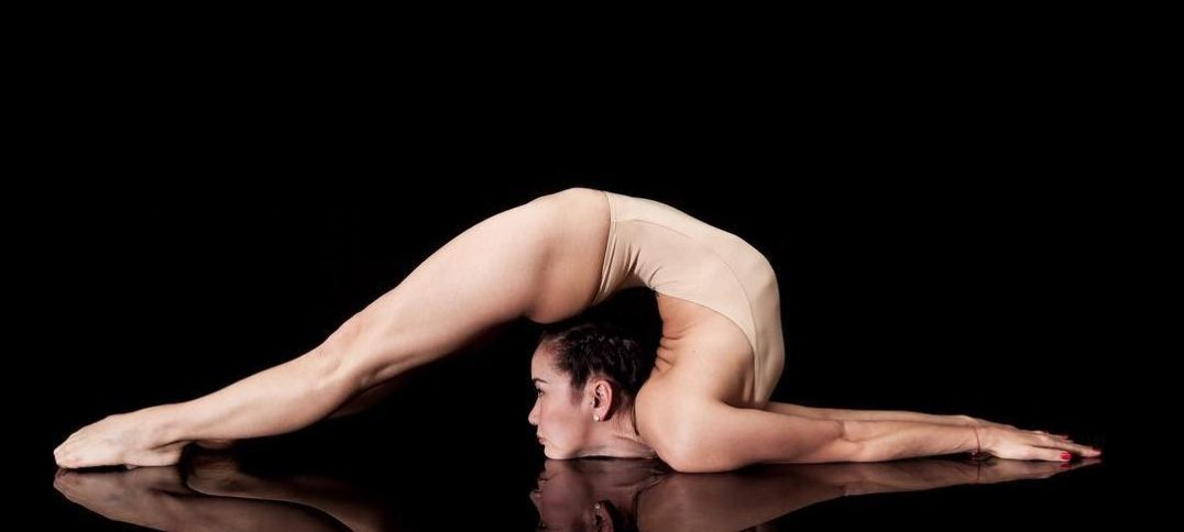 Contortionist Bayar Mabella in headsit chest stand pose