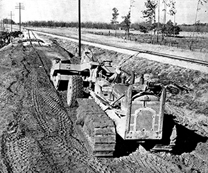 TD-18A equipped with Bucyrus-Erie B-170 scraper prepares a railroad spur in Albany, Georgia, USA, 1951. The machine is also fitted with a Bucyrus-Erie cable frame for a bulldozer which has been removed to allow both drums of the rear mounted cable control to be used. (Author's collection)