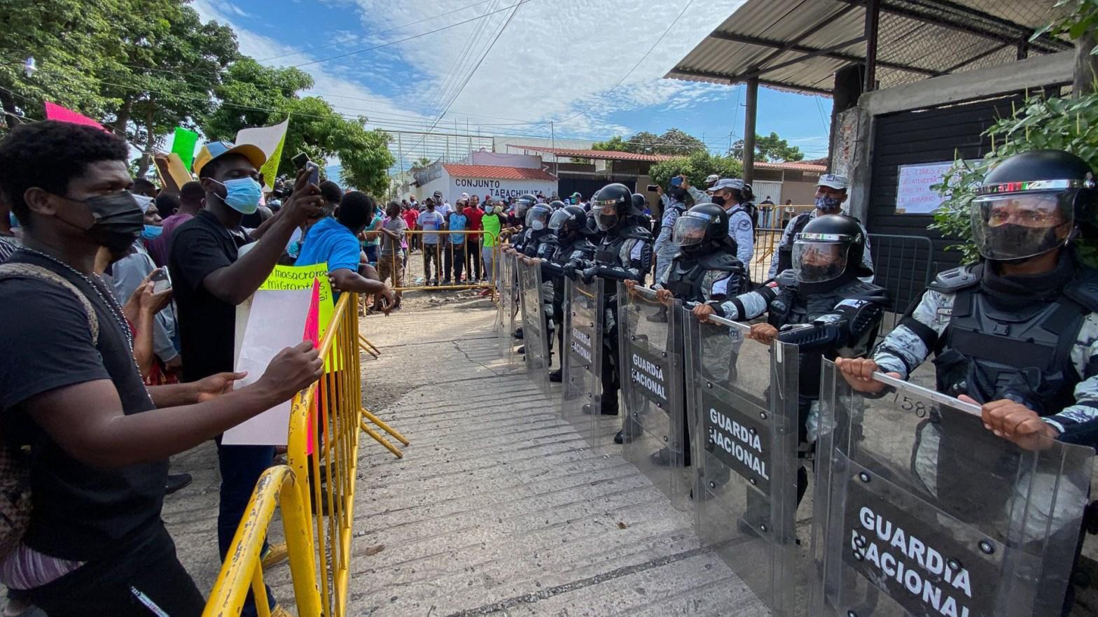 foto de migrantes frente a una fila de integrantes de la guardia nacional