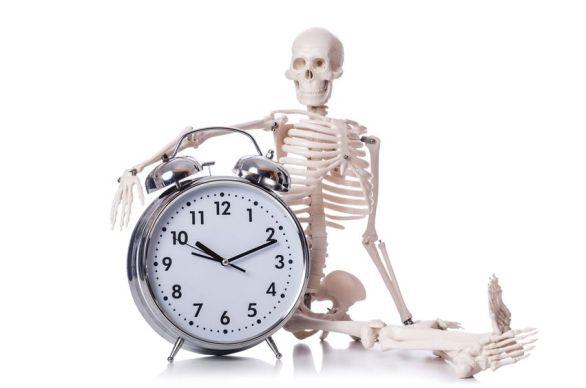 Esqueleto abrazando a un reloj