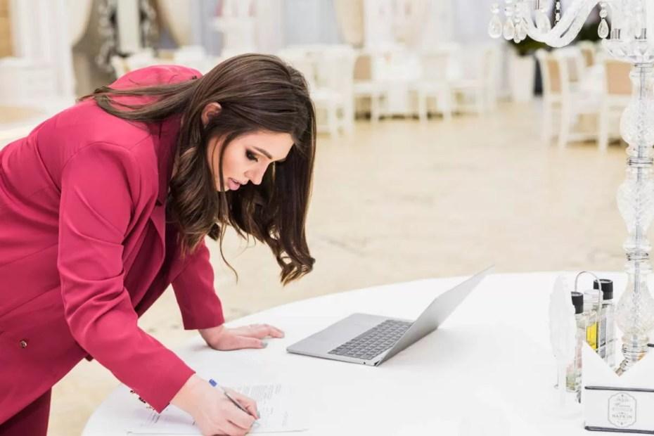 Execução de eventos O que é preciso event-manager-writing-on-paper-in-banquet-hall