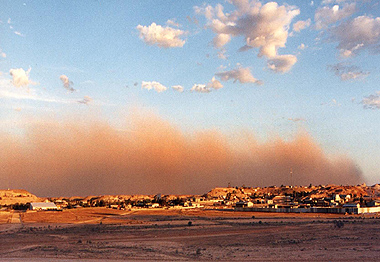 A dust storm rolls in from the south west across the township of Coober Pedy in the late afternoon
