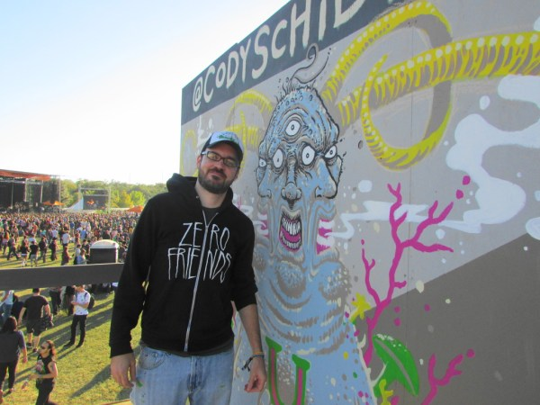 Cody next to his mural.