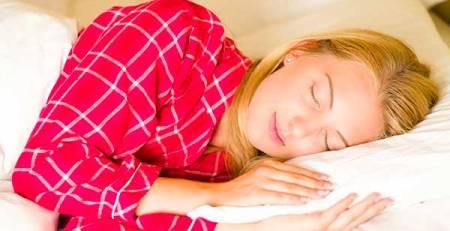 donna dorme letto cuscino