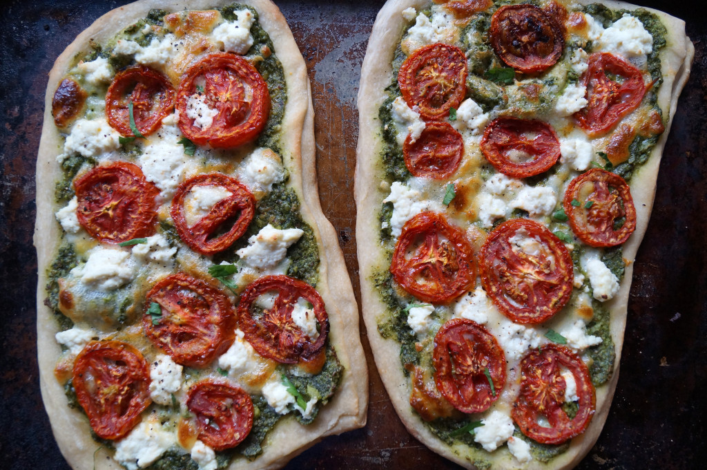 Pesto Pizza topped with oven roasted tomato slices and ricotta cheese- finished