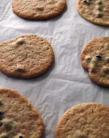 Chocolate chip cookies on a parchment lined baking sheet.