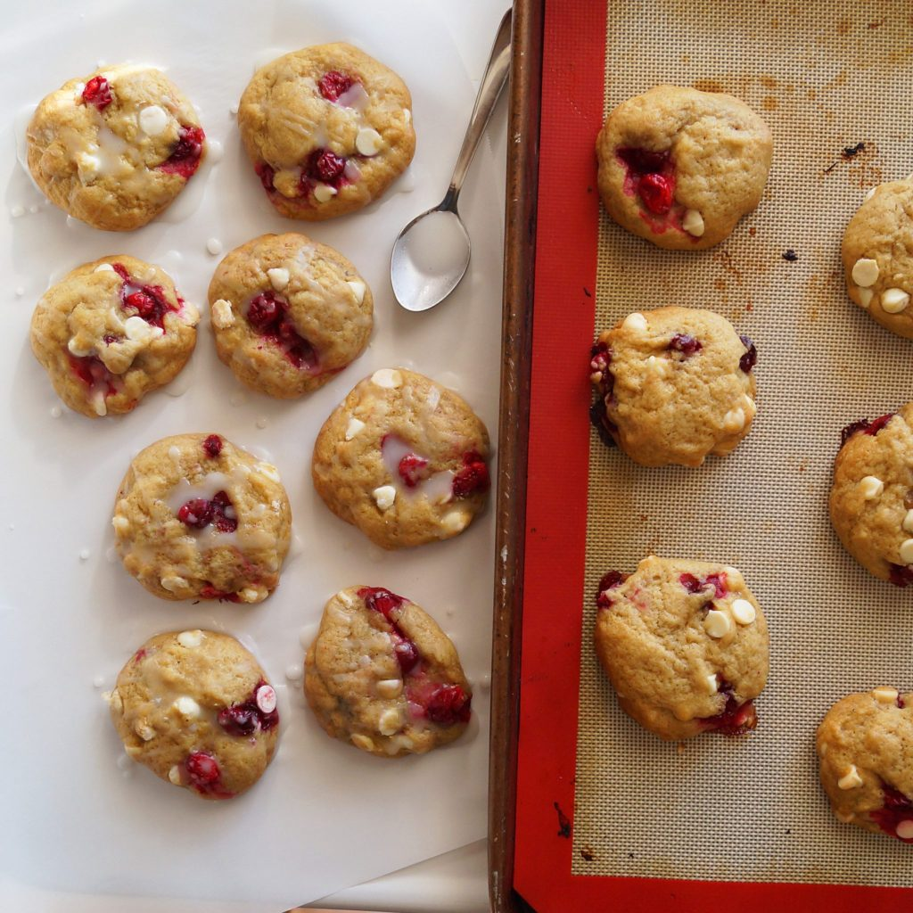 Cranberry Cookies on a white board with a spoon drizzling orange glaze on top.