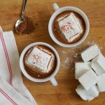 Two white cups filled with Dairy Free Hot Cocoa, topped with Peppermint Marshmallows
