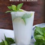 "Side view close up of a tall glass filled with the drink, garnished with lime and fresh mint with the words ""Coconut Mojito Mocktail"" for Pinterest."