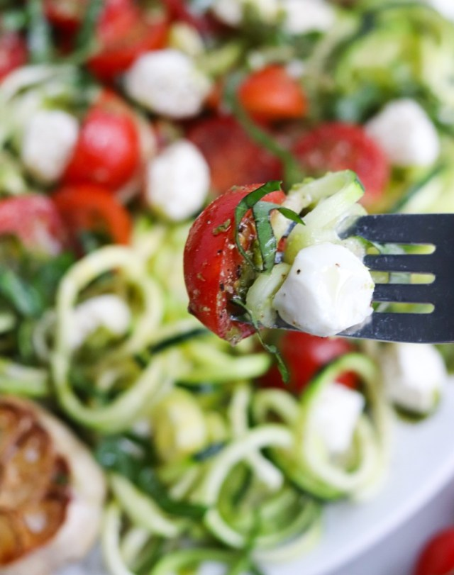 A close up shot of one single bite of salad on a fork.