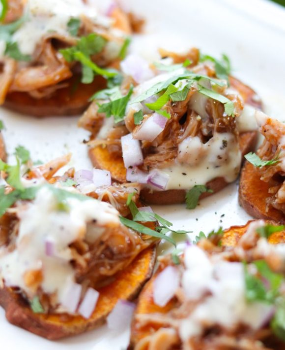 Close up of the Whole30 compliant roasted sweet potato rounds topped with bbq chicken, red onion, ranch, and cilantro.