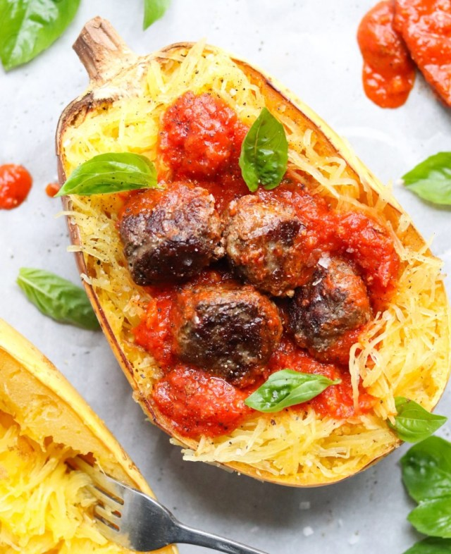 A finished dish with meatballs served inside a cooked spaghetti squash half.