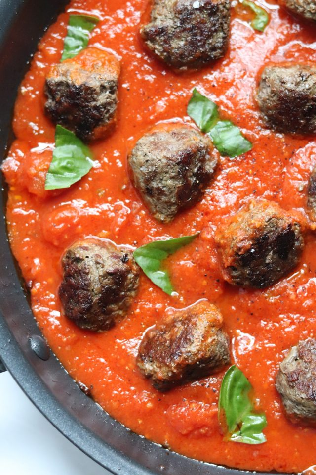Whole30 compliant meatballs sit cook in a red tomato sauce with torn basil leaves - ready for the spaghetti squash!