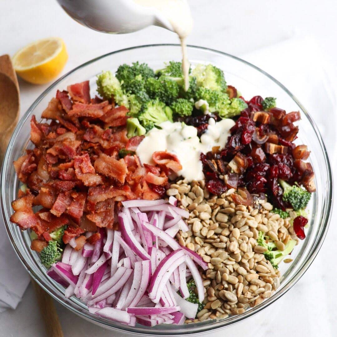 Broccoli and Bacon Salad with Lemon Garlic Dressing, finished dish. The salad ingredients are all in a large glass bowl, and the creamy salad dressing is being poured onto the mixture.