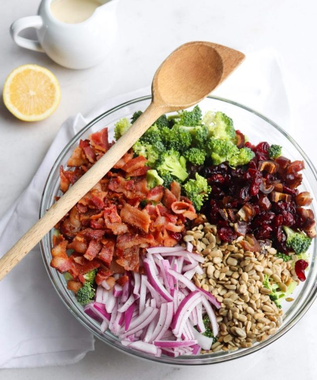 Broccoli Bacon Salad - Finished Dish. A large glass bowl sits on a white marble board. The bowl is filled with bite sized pieces of broccoli, chopped bacon, sliced red onion, sunflower seeds, and diced dates. A large wooden spoon is ready to stir the whole thing up!