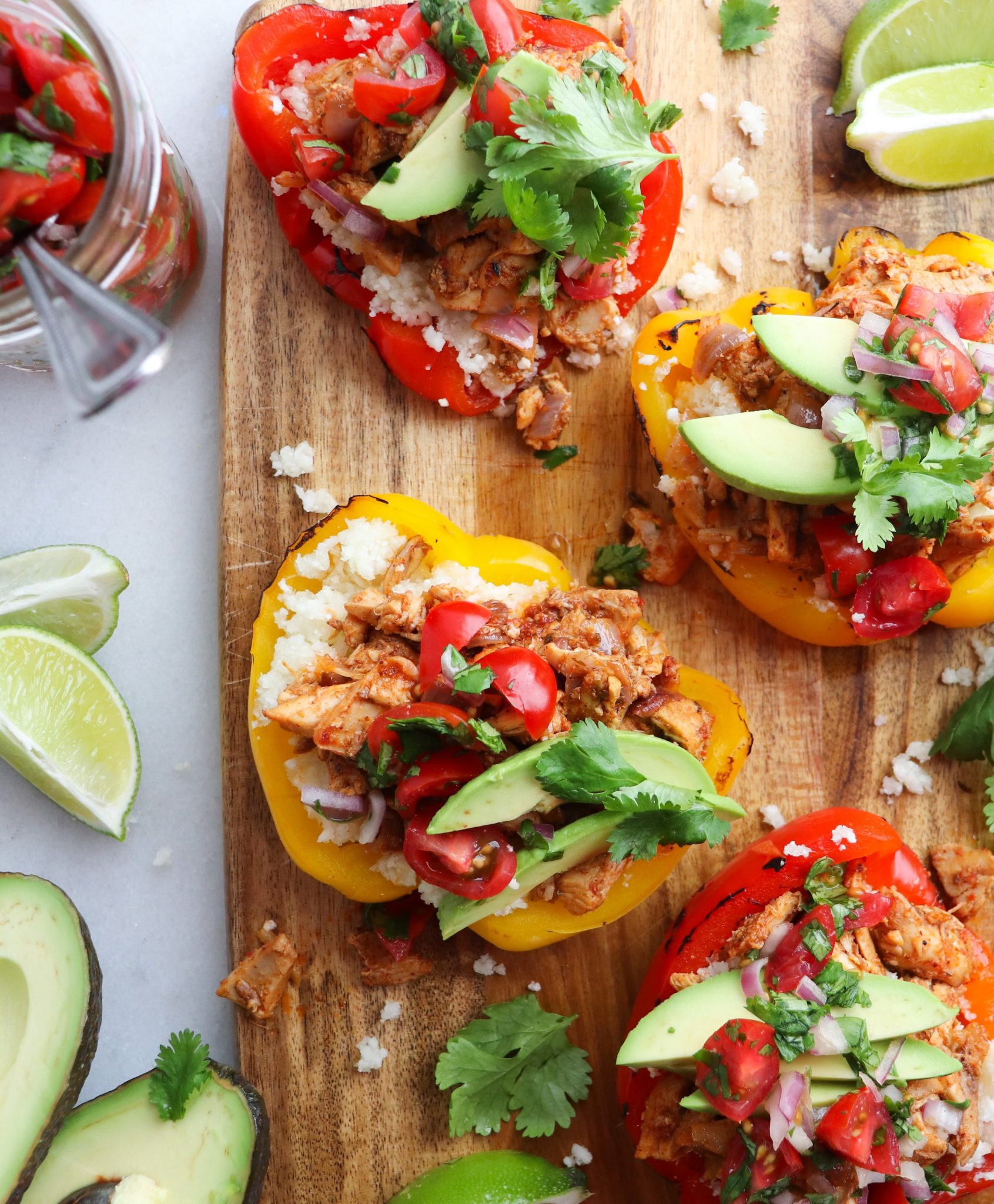 Close up of stuffed fajita bell peppers with fresh pico and avocado slices.