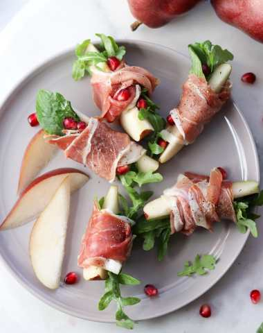 A small gray plate with slices of pear wrapped in prosciutto with a few leaves of arugula tucked inside. Finished Dish