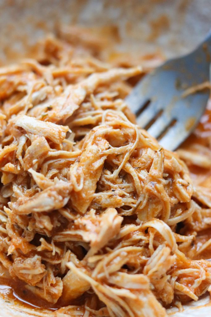 Close up shot of shredded cooked buffalo chicken.