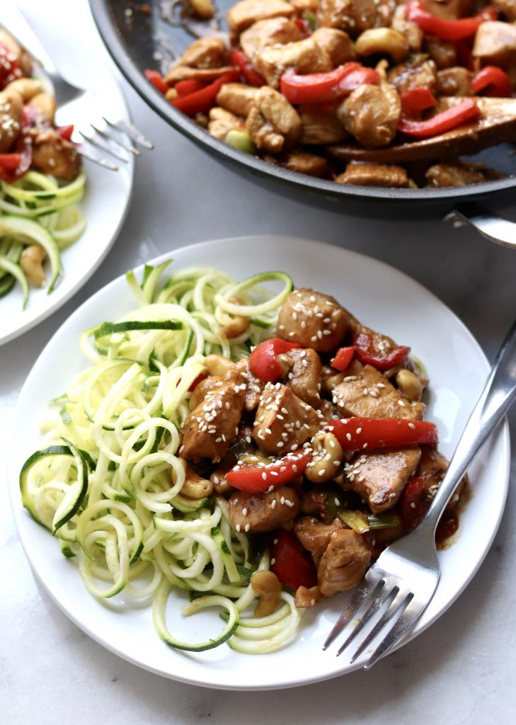 Whole30 compliant Kung Pao Chicken made family-friendly (and LOW CARB!) is served on a white plate with side of raw zucchini noodles. A fork sits on the plate.