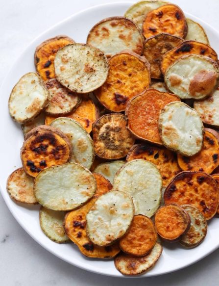 Whole30 compliant roasted rounds of sweet potatoes and white potatoes arranged on a large white plate, ready for the nacho goodness to begin!