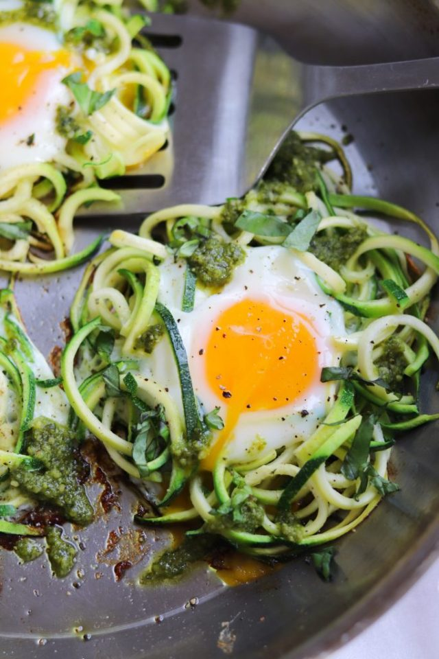 Close up of low carb pesto and spiralized zucchini egg nests in a skillet.