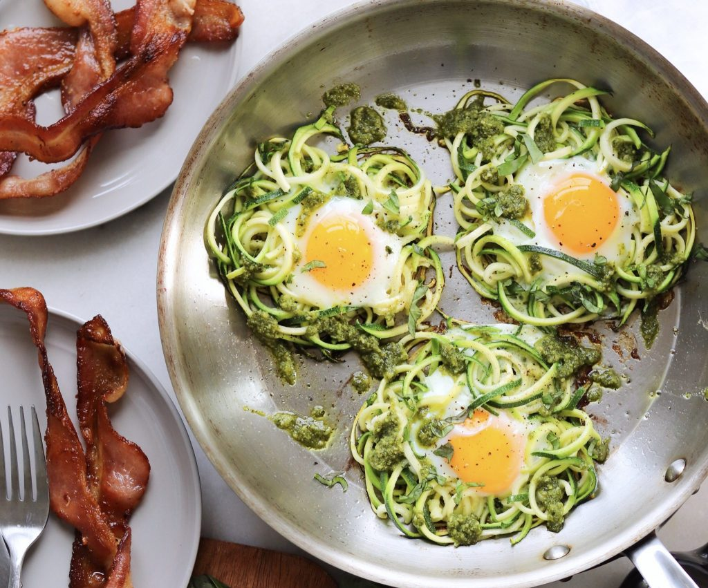 Low Carb pesto and spiralized zucchini egg nests in a skillet, served next to a plate of bacon.