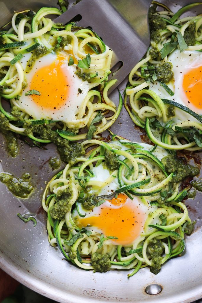 Close up of zucchini nests cooking in a skillet with fried eggs in the middle.