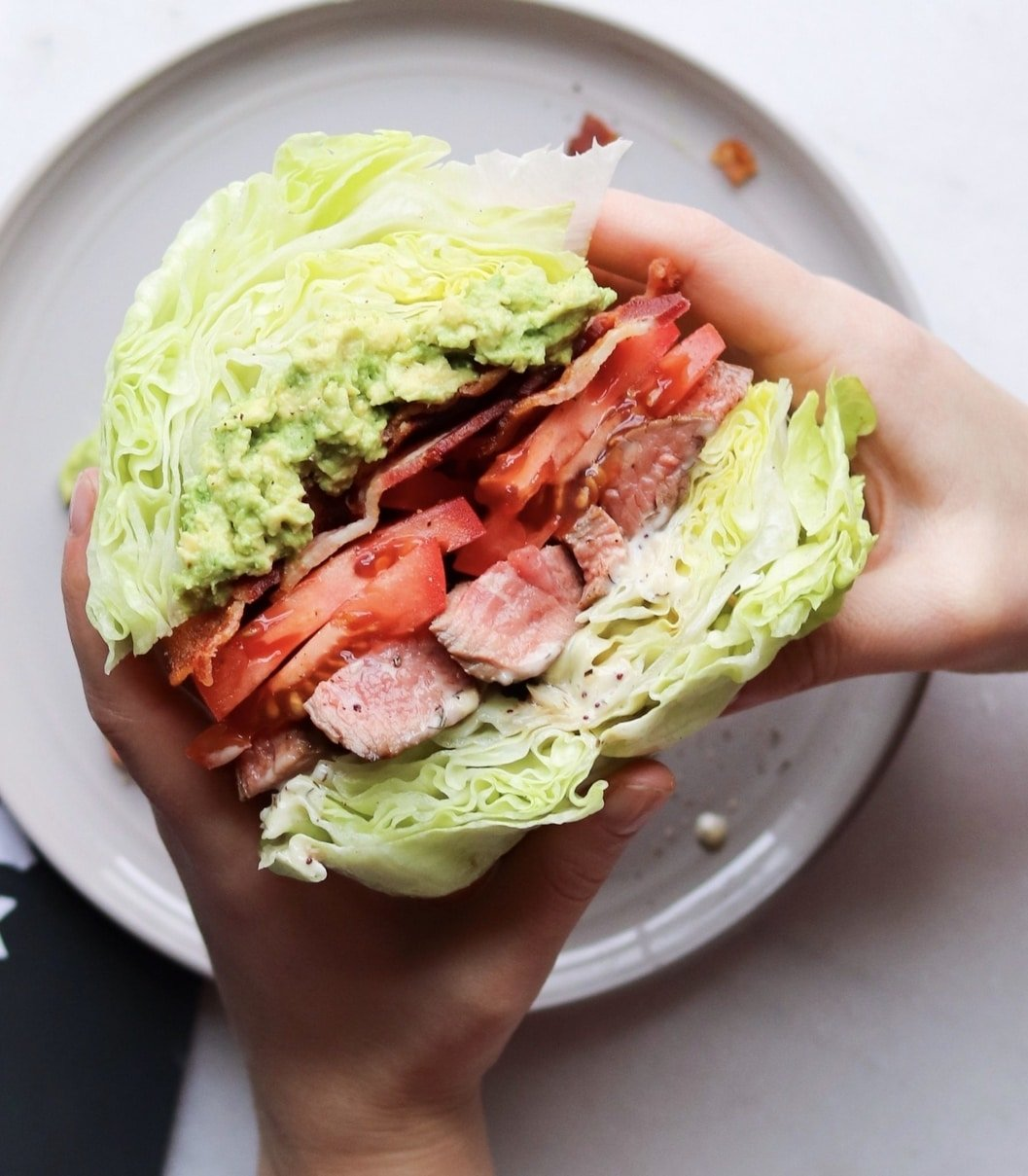 Two hands hold a large lettuce wrapped sandwich full of flank steak, bacon, smashed avocado, and tomatoes.