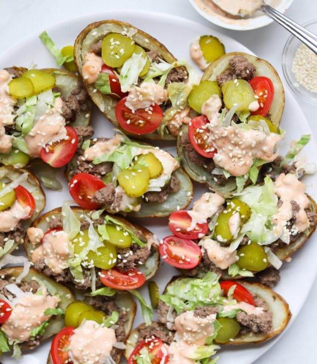 Whole30 Big Mac Potato Skins- Potatoes filled with ground beef, tomatoes, pickled, lettuce, and tomatoes, topped with special sauce and sesame seeds. The potatoes are arranged on a white plate.