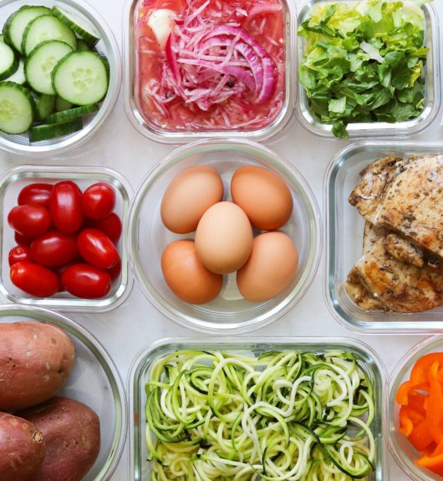 Nine glass containers are each filled with a different batch cooked ingredient: sliced cucumbers, pickled onions, chopped romaine lettuce, cherry tomatoes, hard boiled eggs, grilled chicken, cooked sweet potatoes, spiralized zucchini and sliced bell peppers.