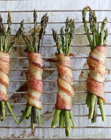 Close up of cooked Bacon Wrapped Asparagus on a metal rack.