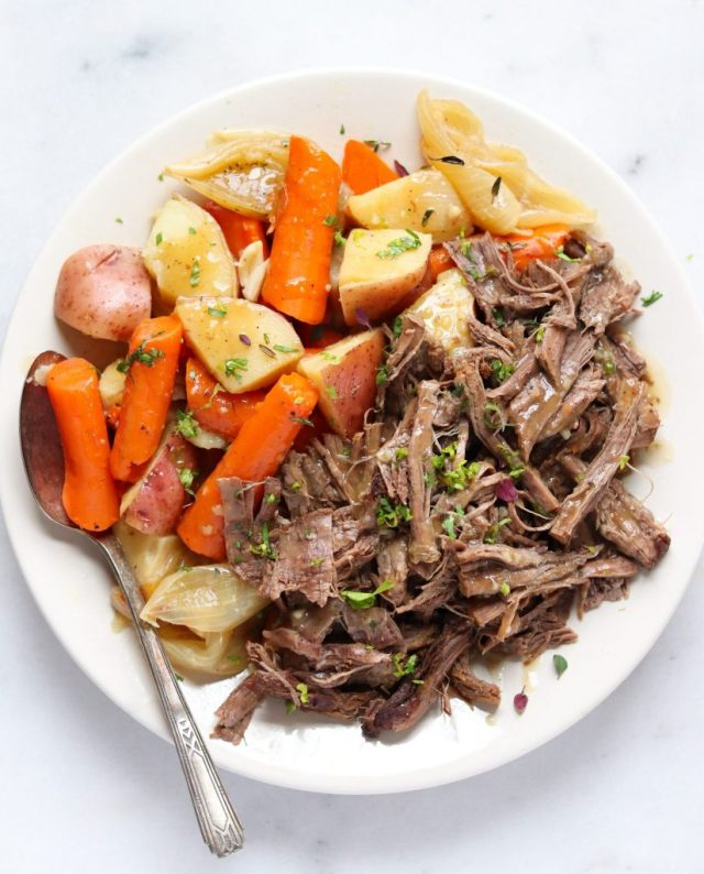 Whole30 Pot Roast, finished dish on a white plate with cooked quartered potatoes and carrots.