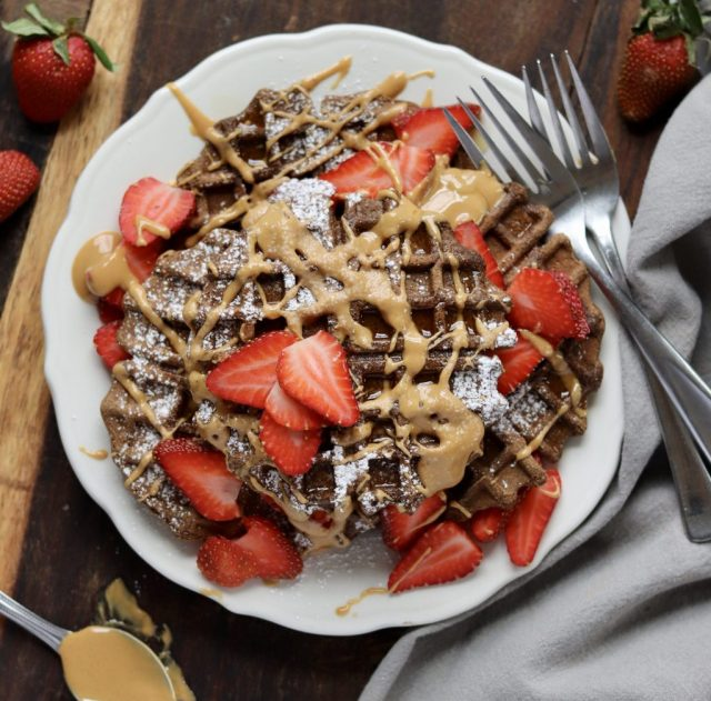 A stack of Paleo Chocolate Waffles drizzled with almond butter and topped with sliced strawberries - finished dish
