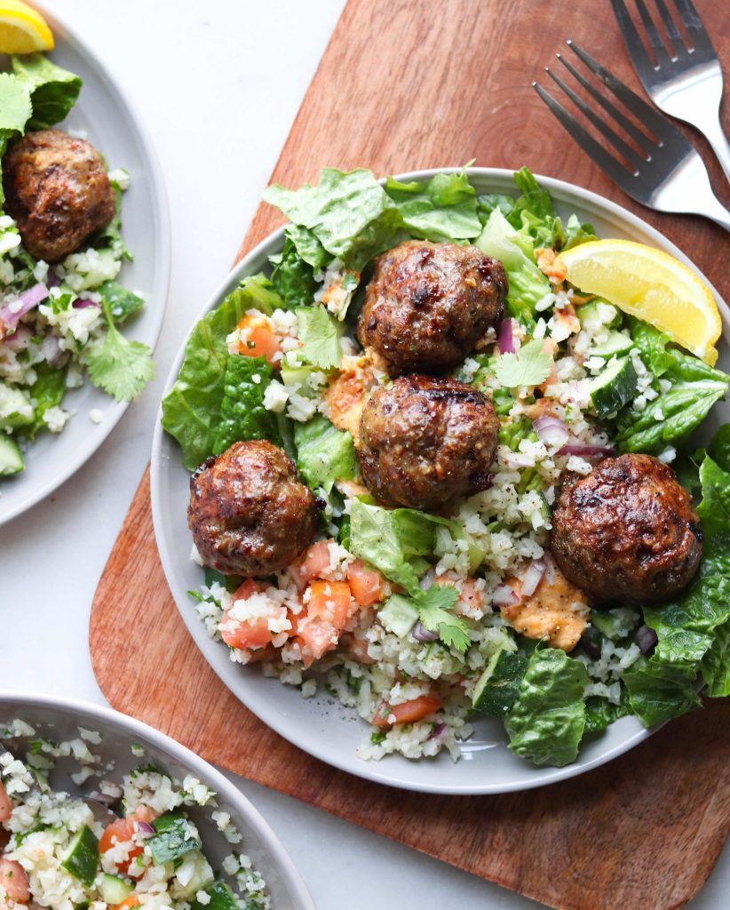 Whole30 Mediterranean Lamb Meatballs are served on a gray plate with torn romaine lettuce, cauliflower tabbouleh, hummus and slices of lemon.