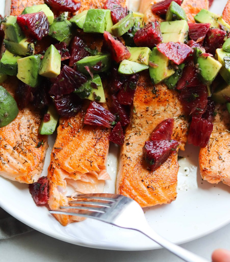 Plated cooked salmon fillets topped with avocado and blood oranges