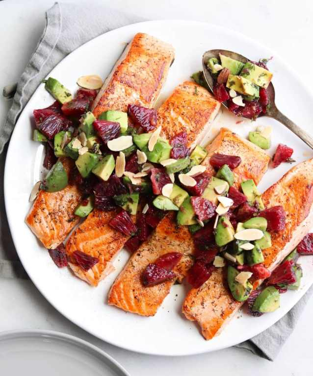 Plated salmon fillets topped with avocado and blood oranges.
