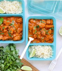 Butter Chicken served in meal prep containers with cauliflower rice. The dish is garnished with cilantro and sliced of lime.