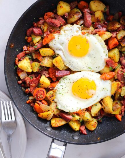 A skillet with corned beef hash and over easy eggs.