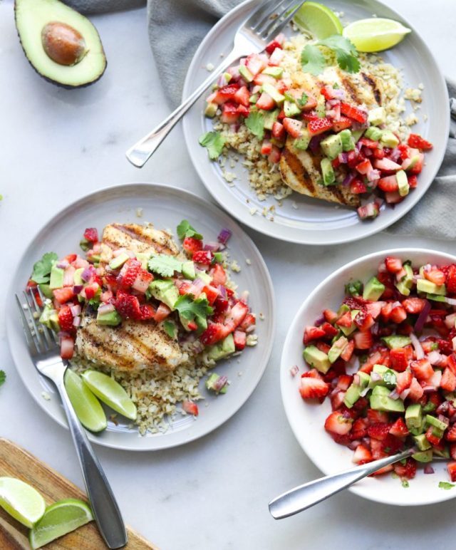 Two plates with Grilled Halibut fillets topped with Strawberry Guacamole and garnished with lime slices. A large white bowl with extra guacamole sits beside the plates.