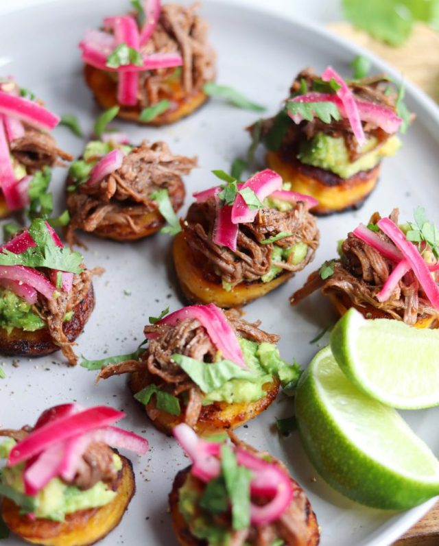 Side view of finished dish. Fried plantains are piled with smashed avocado, shredded Instant Pot barbacoa beef, and pickled onions, then sprinkled with cilantro.