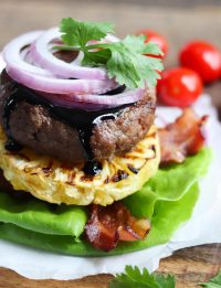 Whole30 Aloha Hawaiian Burgers with homemade teriyaki. The burger is stacked on top of a slice of a grilled pineapple, then topped with bacon, red onion and drizzled with teriyaki